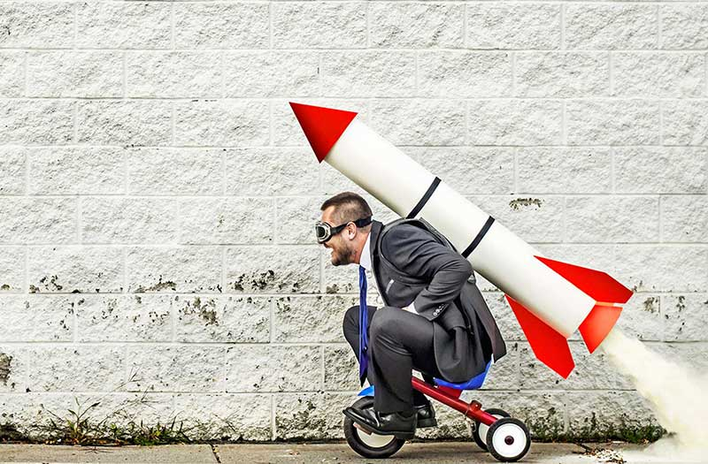 Business man sitting on bike with rocket strapped to his back