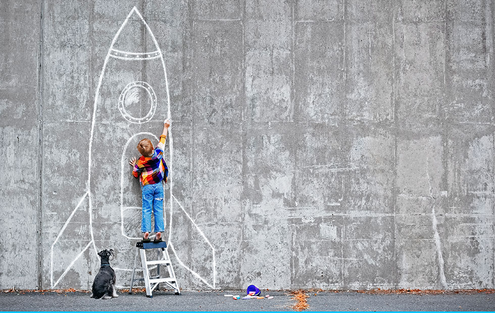 primary school boy drawing rocket on wall