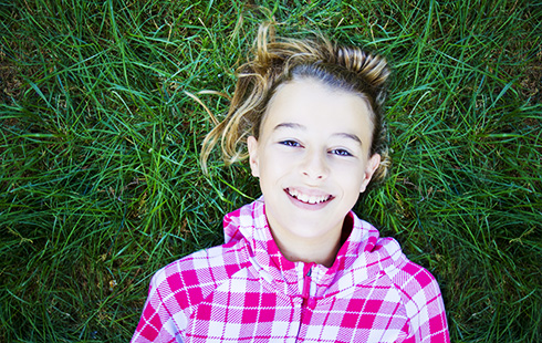happy smiling girl lying on grass