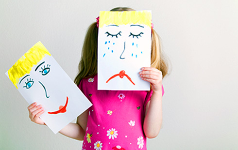 Young girl holding a piece of paper with a happy and sad face drawing